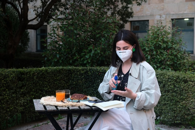 Woman disinfecting hands on a terrace