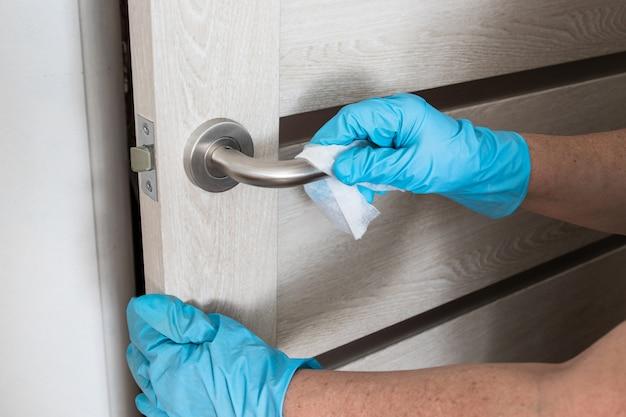 Женщина дезинфицирует и очищает дверную ручку с помощью антибактериальных влажных салфеток для защиты от вирусов, микробов и бактерий во время коронавируса.