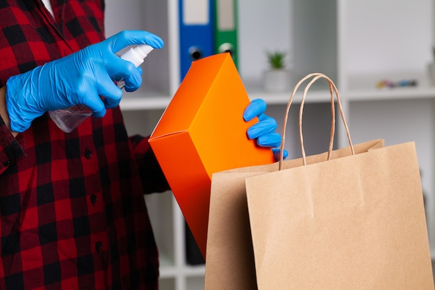 Woman disinfects parcels before unpacking at home