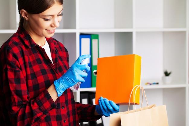 Женщина дезинфицирует пакеты с антисептиком в домашних условиях перед распаковкой
