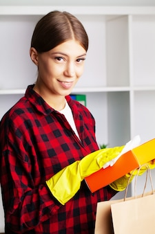 Woman disinfects parcels with antiseptic at home before unpacking