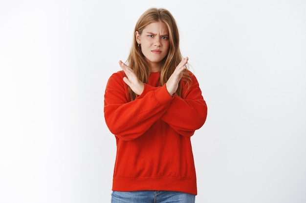 Woman dislikes smokers, making cross against body showing negative opinion about bad habits, frowning and making displeased grimace making stop gesture, rejecting and prohibiting nasty actions