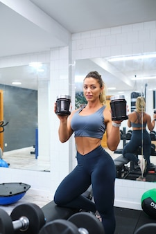 Woman displays jars of protein supplements for athletes in a gymnasium