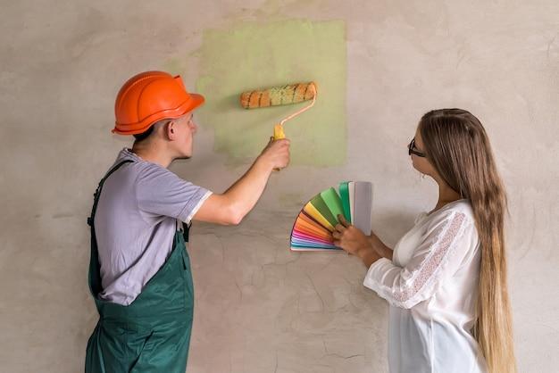 벽의 선택된 색상에 방해받는 여성