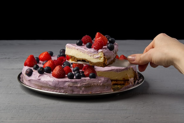 女性はチーズケーキを分け、それを提供するために1つのスライスを取ります。イチゴ、ブルーベリー、ラズベリーの自家製チーズケーキ。