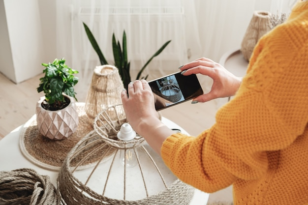 Woman diy blogger takes a photo on a mobile phone for diy blog in social media handmade jute rope lamp