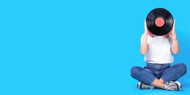青い背景のビニールレコードと女性djの肖像画。ビニールレコードを持つ女性のレトロな写真。ワイドバナー