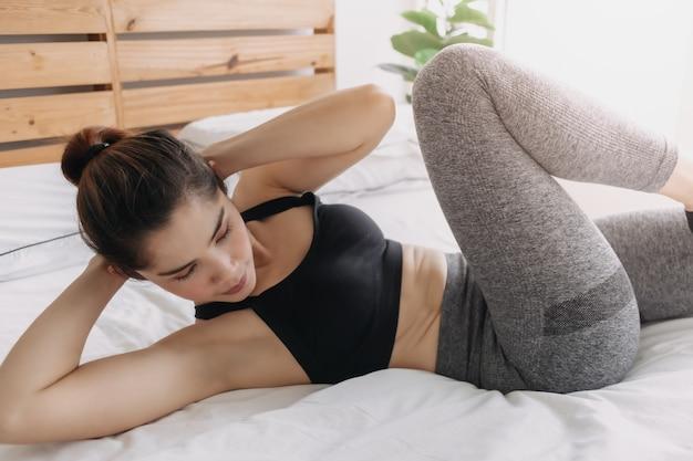 Женщина делает упражнение на скрещивание тела в своей спальне