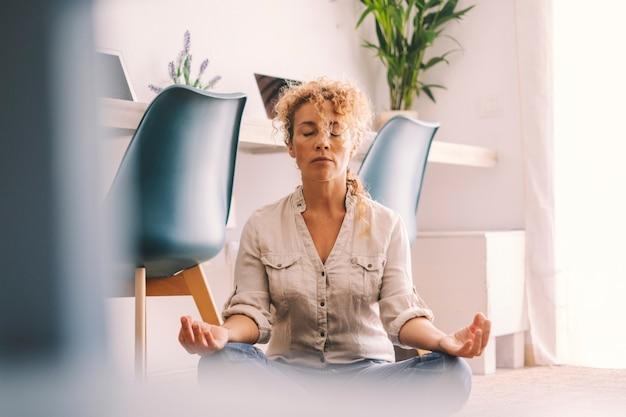 女性はリラックスして健康を保つために自宅でロトポジションを行います。床に座っている大人の女性のための屋内でリラックスした活動。リビングルームの家のインテリアと女性