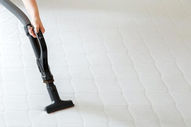 女性は汚れたほこりの細菌から掃除機でマットレスをプロのクリーニングを行います。女性の手の掃除機は、ホテルのアパートの表面、清潔さを消毒します。スペースをコピーします。