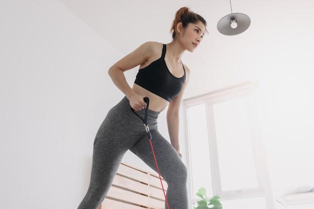 여자는 침실에서 저항 밴드를 사용하여 잔디 깎는 운동을 합니다.