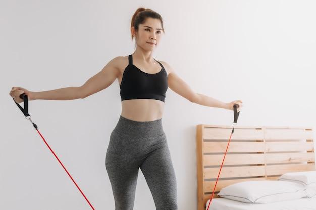 여자는 침실에서 저항 밴드 상부 가슴 압박 운동을 한다