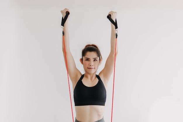 Женщина делает тренировку на жим верхней части груди с эспандером в своей спальне