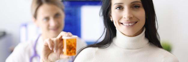 Женщина-врач и пациент улыбаются и держат банку с таблетками. лекарства для профилактики концепции