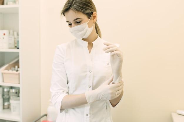 Женщина-врач косметолог надевает одноразовые перчатки на руки