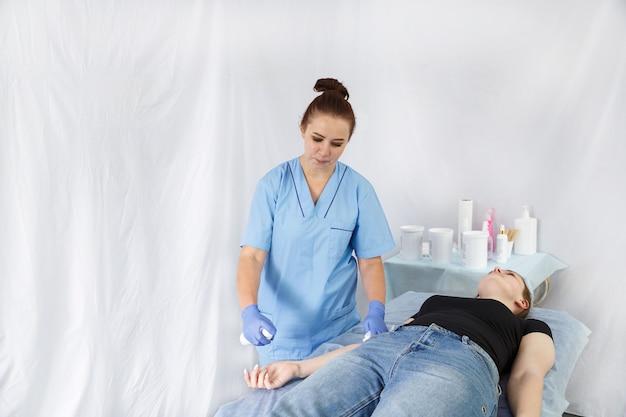 여자 의사 미용사 여기 스프레이와 젊은 여자를 취급