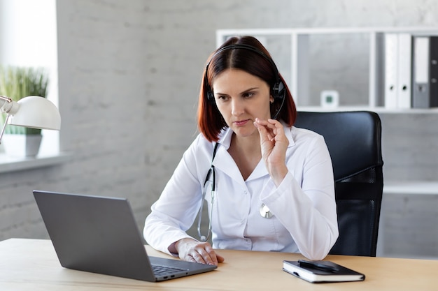 Woman doctor consults by video call online medical assistance.