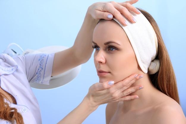 女性医師の美容師は、若い女の子の肌を調べます。美容トリートメントの準備。