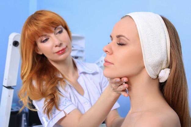여자 의사 미용사, 어린 소녀의 피부를 검사합니다. 뷰티 트리트먼트 준비.