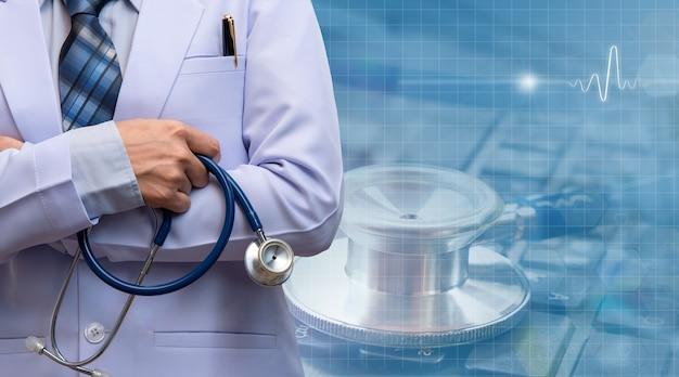 女性医師が腕を組んで聴診器を持ってぼやけた患者部門、医療概念