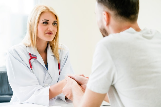 Woman doctor doing handshake with male patient in hospital office room.