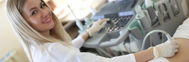 Женщина-врач делает ультразвуковое исследование почек пациентке в клинике