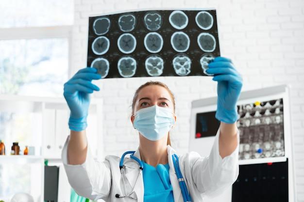 女性医師が病院のクローズアップで頭部mriスキャンを検査します