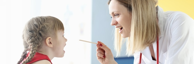 クリニックでへらを持った少女の喉を調べる女医。子供の風邪の治療の概念