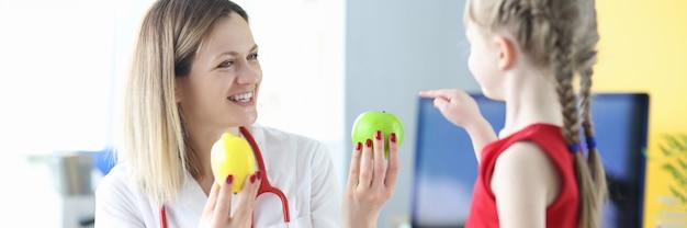 クリニックで小さな女の子に果物を与える女医。子供のための適切な栄養の概念