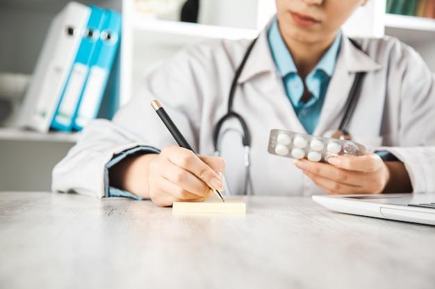 机の上の紙で女医手薬