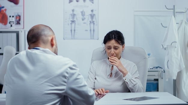 Woman at doctor hearing news about her incurable disease, she starts crying, is lost, depressed. bad news about terminal patient. cancer or other terminal ill concept