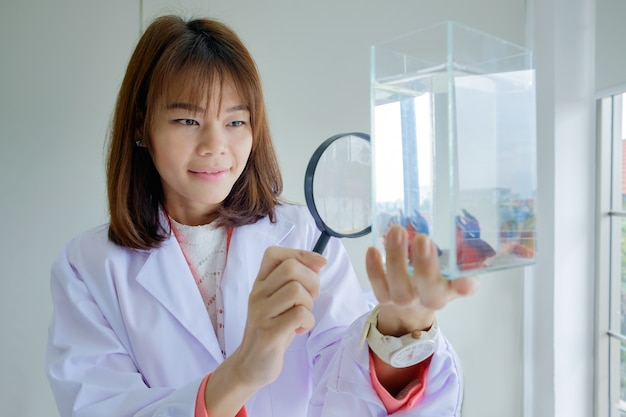 Woman doctor hold magnifying glass looking fish in tank