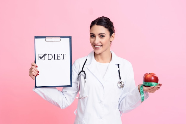 Woman doctor holding apple, measuring tape and diet sign
