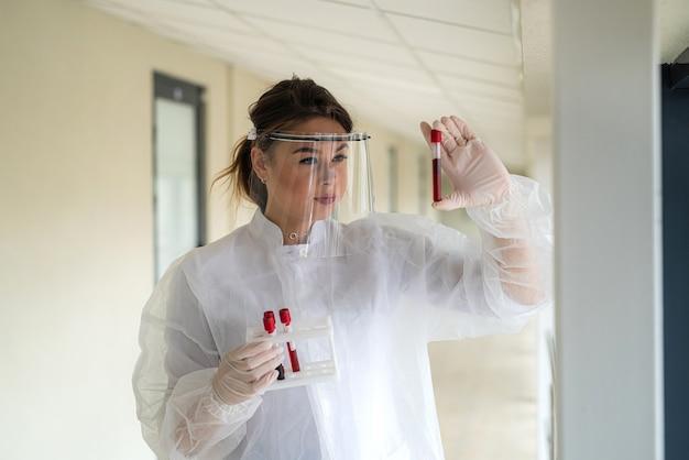 실험실에서 연구 covid-19에 대한 테스트 튜브에 혈액 샘플을 들고 여자 의사