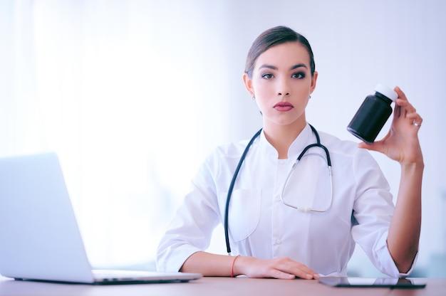 알 약 패키지를 들고 여자 의사입니다. 비타민 병원 노동자