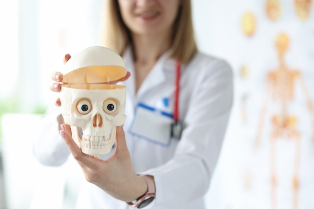 Woman doctor holding plastic model of human skull in her hands closeup