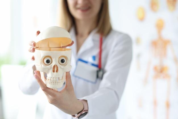 그녀의 손 근접 촬영에 인간의 두개골의 플라스틱 모델을 들고 여자 의사