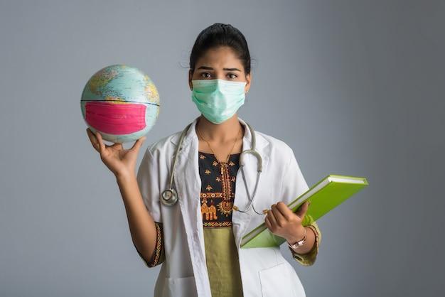 地球儀と本または医療用フェイスマスクでレポートを保持している女性医師。コロナウイルス概念の世界的流行。