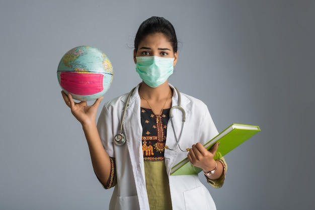 Woman doctor holding world globe and book or report with a medical face mask. world epidemic of coronavirus concept.