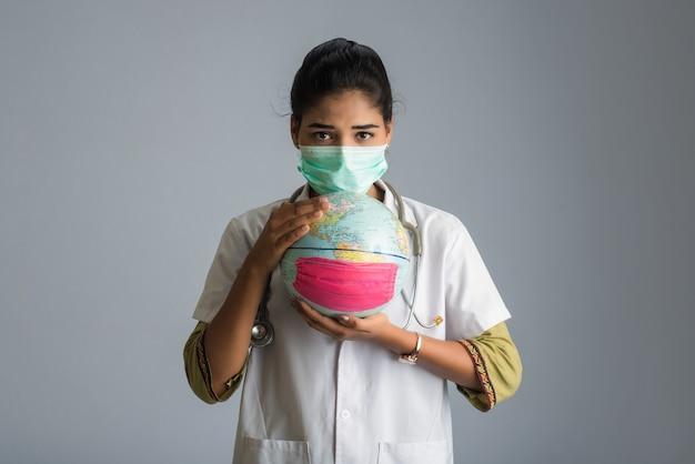 女医が薬のフェイスマスクで地球儀を保持しています。コロナウイルス概念の世界的流行。