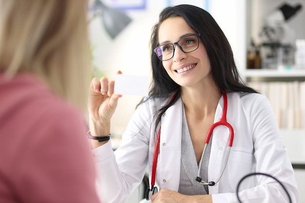 여성 의사는 환자 의료 보험 및 검사 개념에 명함을 내밀고 있습니다.