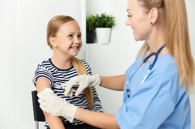 Женщина-врач в синем халате колет ребенка в руку covid
