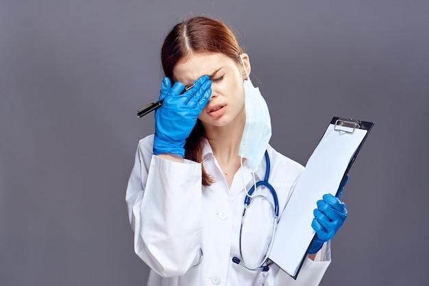 医療ガウンと聴診器と灰色のドキュメントと青い手袋の女医