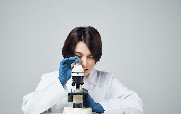 테이블에 현미경으로 의료 가운에 여자 의사는 밝은 방의 자에 앉는 다.