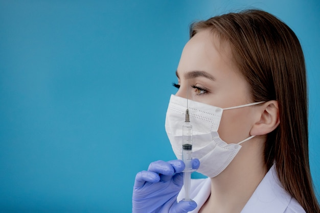 白い医療コート、マスク、帽子、手袋の女医は、彼女の手に薬と注射器を保持しています。白い背景の上に立って