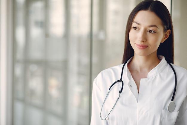 홀에서 흰색 유니폼 서에서 여자 의사