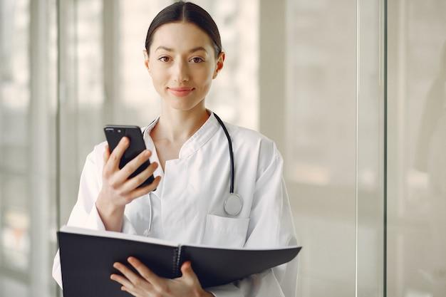 Женщина-врач в белой форме, стоя в зале