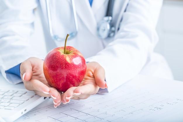 Женщина-врач в машине скорой помощи держит в руках красное яблоко. на настольном ноутбуке и диаграмме экг.
