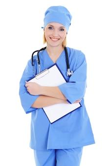 チャートを保持している青い医療制服の女医-白で隔離