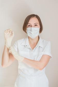 Женщина-врач в перчатках и медицинской маске